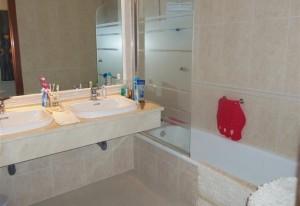 Slaapkamer 1 beschikt over een ligbad, toilet en 2 lavabo's